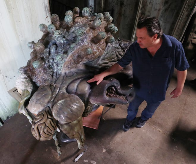 """David Barton looks over the detail of the of the skin as he talks about the newly acquired, Kaiju organ which rest an autopsy table, that is a prop from the film """"Pacific Rim"""" at Ghoul Brothers House of Horror Thursday June 10, 2021 in Akron."""