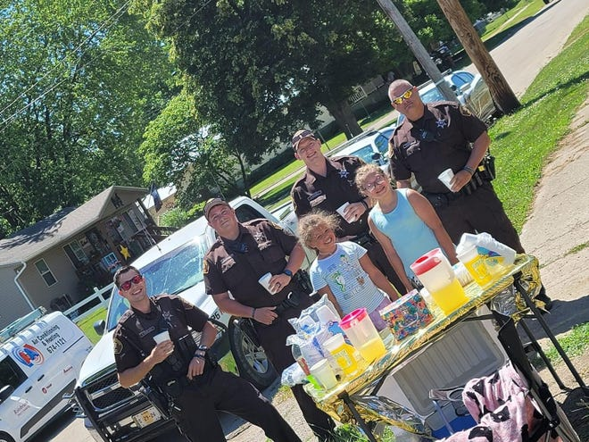 The Kelson sisters are pictured with Fulton County Sheriff's Deputies who purchased lemonade from the duo. Also stopping by were other first responders including Canton Police and firefighters.