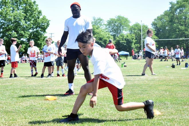 Kansas City Chiefs wide receiver Tyreek Hill watches a youth football camp attendee perform a drill on Sunday at Cosmo Park in Columbia