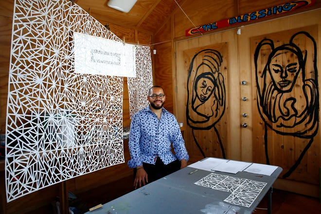 Johnathan Payne is the first Aminah Robinson House resident artist. He is pictured with his artworks in the studio of the home on Monday, June 14, 2021.