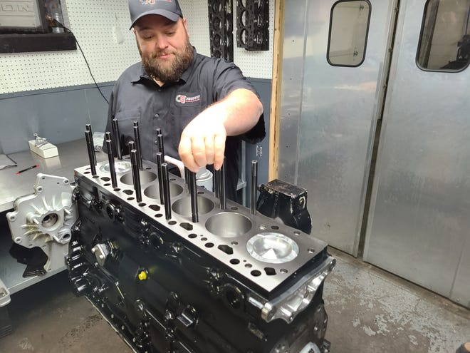 Owner Drew Pumphrey of D&J Precision Machine works on a diesel racing engine at the business on Woodlawn Avenue in Cambridge. D&J Precision received the Excellence Award at the annual Eastern Ohio Development Alliance meeting last week.