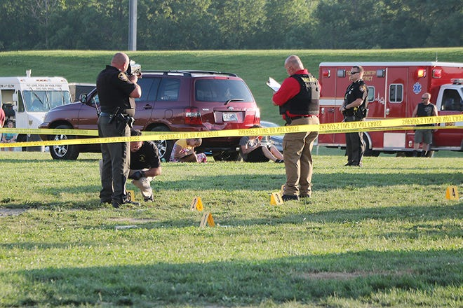 Detectives from the Wayne County Sheriff's Office collect evidence at the scene of a shooting that took place on Sunday at Dragway 42.