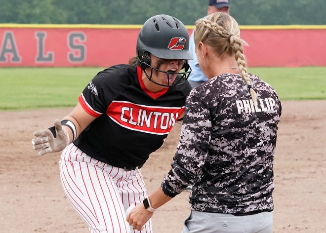 Clinton's Lily Thompson celebrates a bases-clearing triple with head coach Kim Phillip at third during the Division 3 regional semifinal game Saturday against Napoleon.