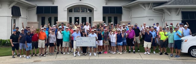 Attendees for the 2021 Golf Gala pose with a donor holding a check for a $65,000 donation to the foundation.
