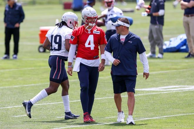 New England Patriots quarterback Jarrett Stidham (4) talks to offensive coordinator Josh McDaniels during OTAs at the New England Patriots practice complex on June 10, 2021.