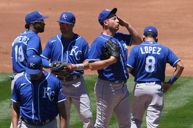 Kansas City Royals pitcher Kris Bubic, middle right, reacts on the mound after a visiting by pitching coach Cal Eldred, bottom left, during the second inning of Sunday's game against the Oakland Athletics in Oakland, Calif. The Royals lost 6-3 for their eighth loss in nine games.