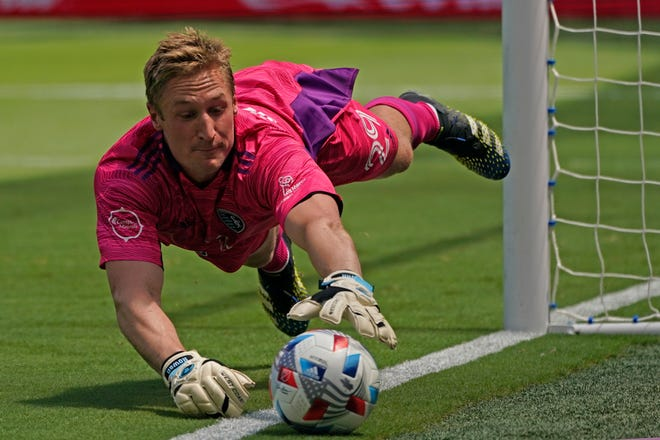 Sporting Kansas City goalkeeper Tim Melia dives to keep the ball inbounds during the first half of an MLS soccer match against Austin FC Saturday at Children's Mercy Park. MLS and Liga MX have partnered for an all-star game but have not discussed a merger of the two North American leagues, though they're not ruling it out.