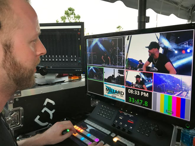 Video producer Matt Brown of Broken Centrifuge Productions directs live cameras during a performance by songwriter Shy Carter, seen on-screen, at the June Summer Concert Series on Burlington's riverfront. Brown is treasurer of Burlington Riverfront Entertainment, the producers of the show. The next Summer Concert Series is set to begin Friday.