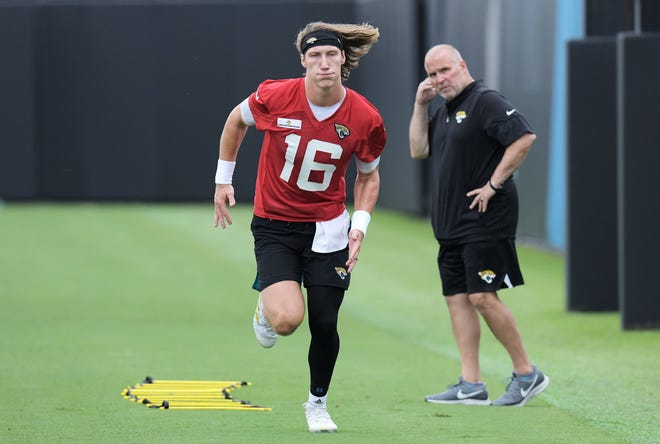 Jaguars' quarterback Trevor Lawrence (16) goes through pre-practice runs to test his left hamstring Monday under the watchful eye of athletic trainer Pete Draovitch.