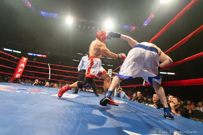 Firefighter Anthony Principe (left) throws a punch at police officer Cody Berk during their 2019 Guns N' Hoses match.