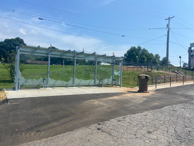 A new Gastonia bus shelter near the Dixie Village Shopping Center on West Franklin Boulevard gives commuters a place to sit while waiting on the bus. An etching on the glass depicts a mountain climber at nearby Crowders Mountain State Park.