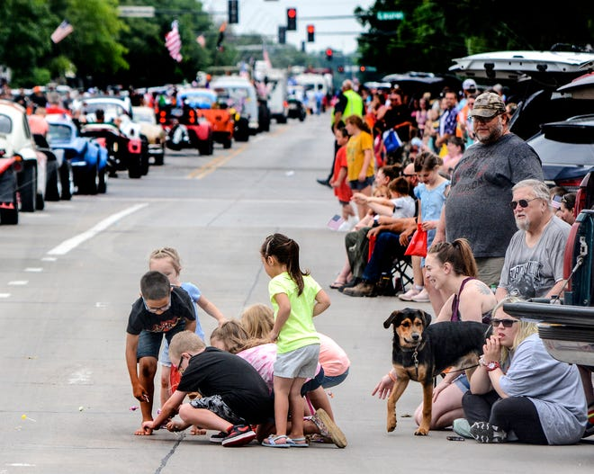 A group of children scramble for candy thrown by a parade participant Saturday morning on Main Street during the Western Motors Beef Empire Days parade. Local residents lined Main Street to watch the parade's return after a year off due to the COVID-19 pandemic.