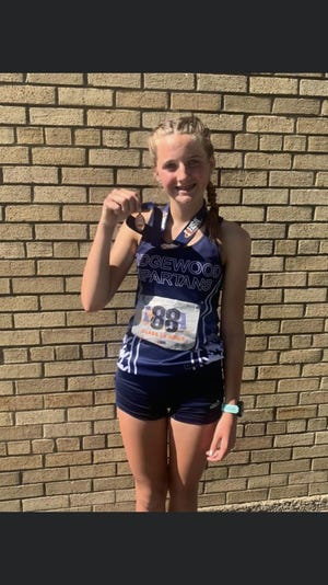 Miranda Reed shows off her seventh place medal in the 3200m.