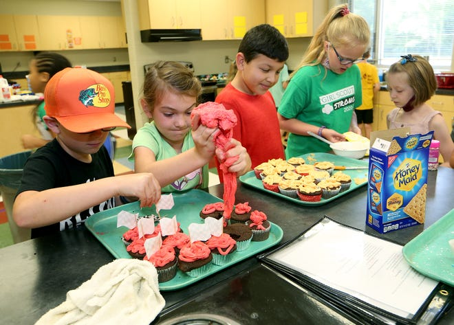 Matthew Schmidt puts on finish line flags as Clara Shank squeezes out frosting onto their Racers Cupcakes during STEAM Camp at Prairie Hills Middle School Thursday.