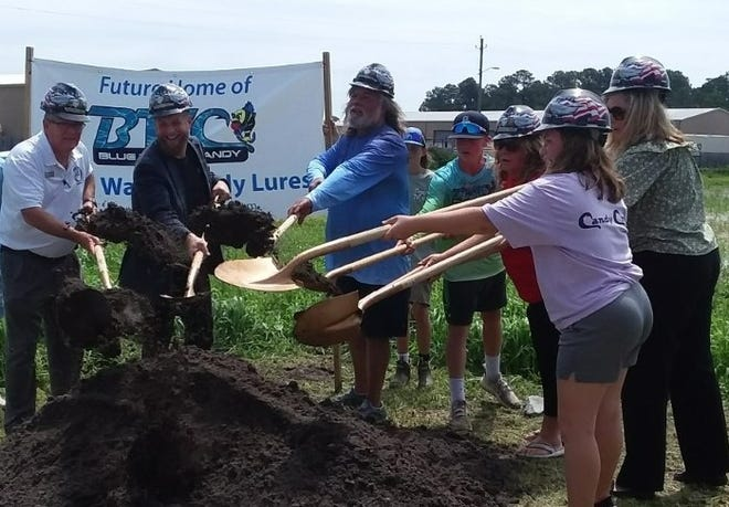 From left: Onslow County Commissioner Royce Bennett, Holly Ridge Mayor Jeff Wenzel, Captain Jodie Gay, grandson Connor Weaver, Terry Gay, JOED Chairman Susan Edwards. In the forefront, granddaughter Taylor Weaver at Blue Water Candy's groundbreaking ceremony in Holly Ridge Friday morning.