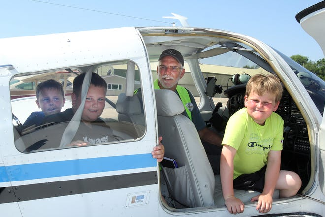 Eli Henderson, right, leans out of an airplane after taking a ride with Pilot John Musser, T.J. Engelbertson, left, and Aiden Thommen at the Freeport Pilot's Association's Young Eagles Rally, Saturday, June 12, 2021, at Albertus Airport in Freeport.