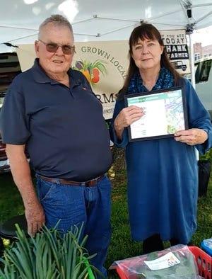 John Greenwood receives his farm market managercertificate and pin from Deborah Cavanaugh-Grant of the Illinois Farm MarketAssociation.