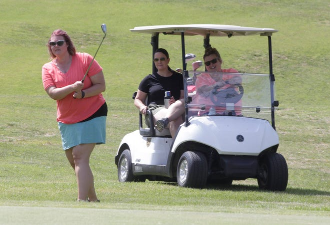 Angela Rash and Megan Jones sit in a golf cart as they watch Danielle Lindsey chip the golf ball onto the green at hole no. 2 as they participate in the Peak Sport & Spine Chipp-in For Kids Golf Tournament held June 8 at Heritage Hills Golf Course in Moberly. The event raised more than $4,200 that was divided among several school district's athletic depart,ents located within mid-Missouri.