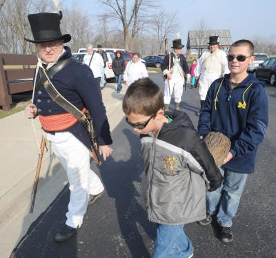 The LaCroix Company under the direction of re-enactor-historian Ralph Naveaux (left) demonstrated how soldiers would bring a yule log into a cabin at midnight on Christmas Eve. Zach Stambaugh, 7, of Petersburg and Jonah Wilson, 14, of Rossford, Ohio, help carry the log at the River Raisin Battlefield's Frenchtown Christmas program in 2012.
