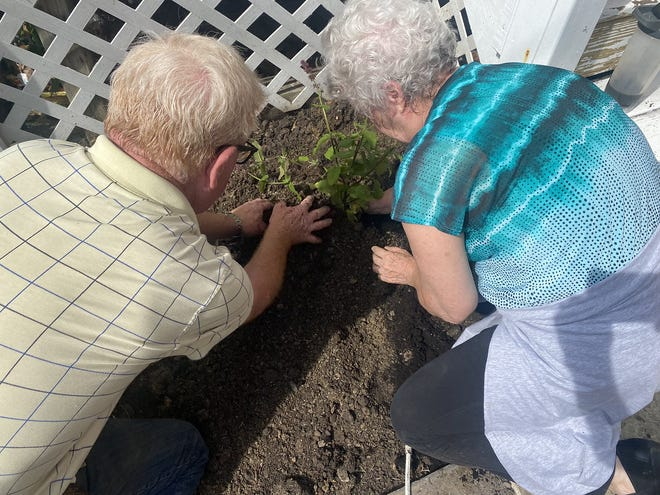 Dave Peters and Debbie Cadeau work on landscaping at Selah's House of Hope.