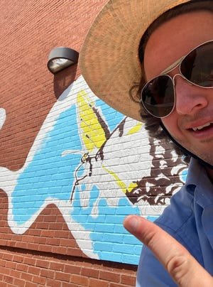 Tim Rand has started the mural on the side of the Palace Theater in Hamilton to celebrate the pollinator garden in Arts at the Palace parking lot.