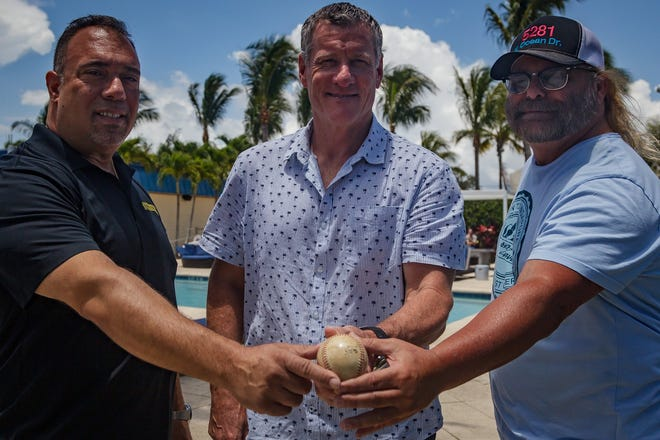 Spero Georgedakis, Jeff Conine and Daniel Taylor (left to right) hold the ball Conine hit for the first home run in Marlins history during the team's first exhibition game in 1993. They met at the Rybovich Superyacht Marina in West Palm Beach last Friday.