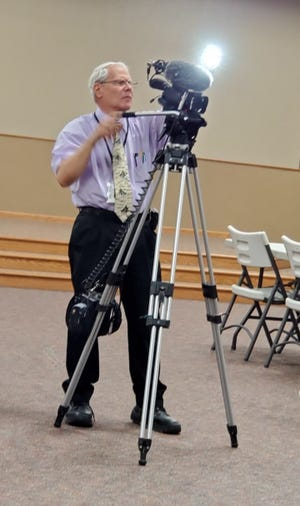 David Cutright runs a video camera for television coverage of an event in St. John. He was the recent 2021 Grand Marshall of the Jubilee Parade in honor of his efforts to improve community connections.