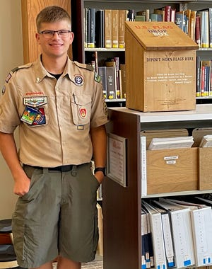 Noah Cottongim stands with the community flag disposal box he made as part of an Eagle Scout project.