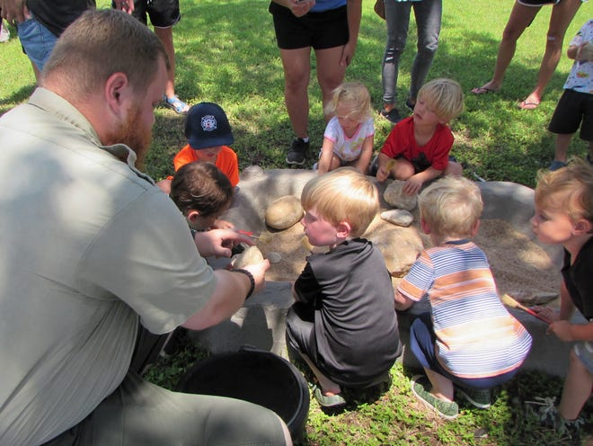 Ranger Allen, from Dinosaur Valley State Park, talks to some youngsters on Thursday during Dino Dig, a special presentation as part of the Stephenville Public Library Summer Reading Program.
