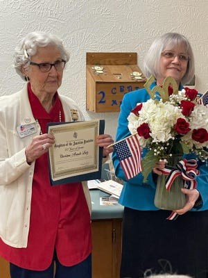 Regent Mary Curtis, right, presents 50-year member Charlene Lietz with flowers and a certificate to honor her service to the chapter.