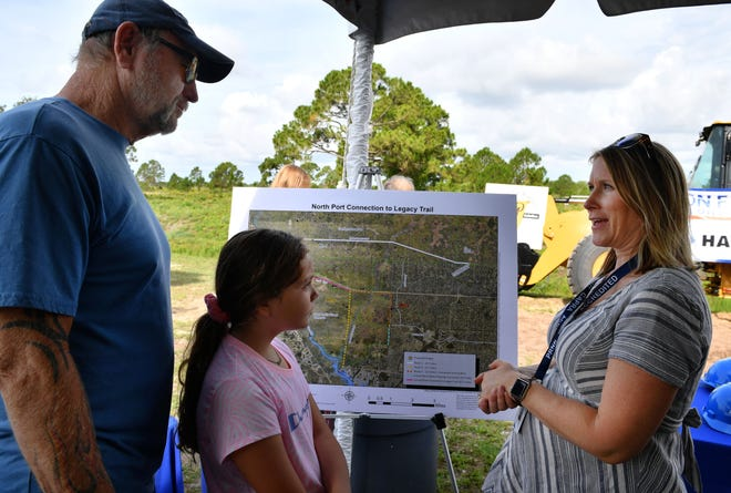 North Port resident Charlie Grandt, and his granddaughter, Taylor Grandt, 9, listen to Megan Eidel as she talks about the future of the Legacy Trail following a ground breaking ceremony Monday morning. Grandt lives one house away from the future site of the Legacy Trail connection at the west end of West Price Boulevard in North Port. Eidel works in Trails Management for the Sarasota County Parks and Recreation department.