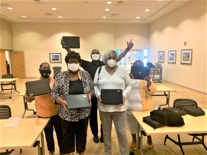 Digital literacy students in Palm Beach County pose with their instructor