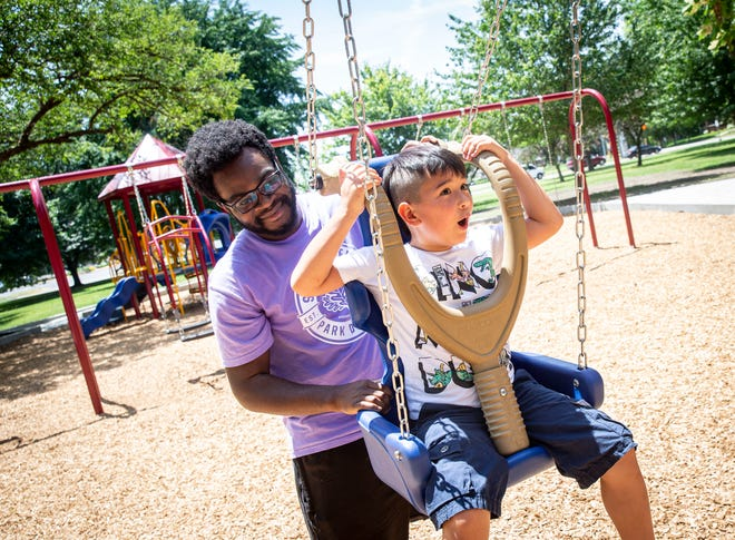 Al Nimpson, camp director for Springfield Park District's Camp L.E.A.P., helps launch Evan Pilar, 7, down the new zip line as they try out the new equipment for the Iles Park playground  after a ribbon cutting in Iles Park in Springfield, Ill., Monday, June 14, 2021.