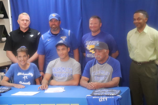 Bethel High School's Dez Loving (seated center) signed a letter-of-intent to run cross country and wrestle at Oklahoma City University. Seated with Dez are his parents Shannon Loving (left) and Gary Loving. Standing are Jeremy Stewart, Bethel High School principal and cross country coach; Coach Joey Ginn, Bethel head football coach; Brandon Blizzard, Bethel track and field coach and assistant football coach; Juan York. Tecumseh High School wrestling coach and coach of Dez in youth wrestling. Not pictured are Bethel High School wrestling coach Jason McPhail and Will McDoulett, his OKUSA wrestling coach who is also a Harrah High School wresting coach.