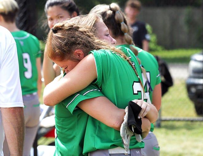 Izzy Smith shares a hug with senior Kiana Gray after the Hornets fell to Kalamazoo Christian in the regional round on Saturday.
