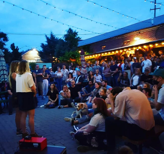 Erika Edwards and Kristi Ray of Honey Head Films speak to a large crowd that packed the courtyard of Wilmington's Satellite Bar & Lounge for the Wilmington Underground Film Festival on June 2. It's one of several local arts events to draw big, ecstatic crowds in recent weeks.