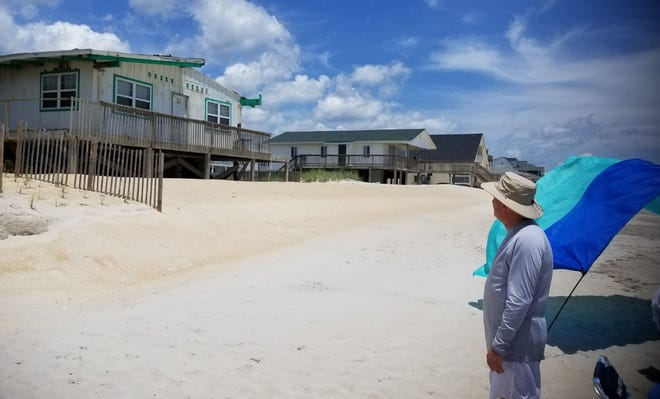 Dan Wright of Raleigh observes an abandoned structure while visiting North Topsail Beach. [CHASE JORDAN / STARNEWS]