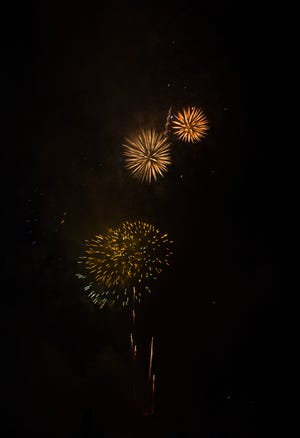 Thousands watch fireworks burst over the U.S.S. North Carolina and the Cape Fear River to celebrate Independence Day on the Riverwalk in downtown Wilmington.
