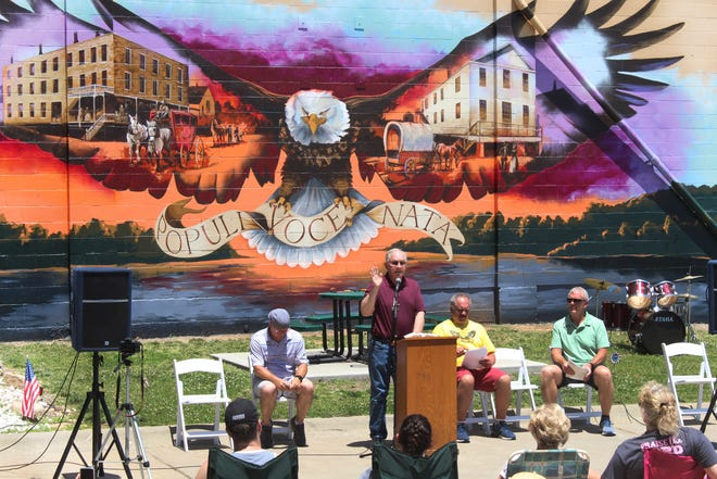 """Paul Bahnmaier, president of the Lecompton Historical Society, speaks during a June 12 dedication of the mural """"Resilience,"""" which was painted by artist Rick Wright on the south side of the former Lecompton High School gym. The mural depicts the town's territorial history inside the outstretched wings of a bald eagle."""