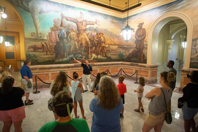 """The famous painting """"Tragic Prelude"""" by John Steuart Curry is shown Monday to a tour group by Norm Hodge, of the Kansas Historical Society. Public tours have officially resumed at the Statehouse, although the dome isn't accessible yet."""