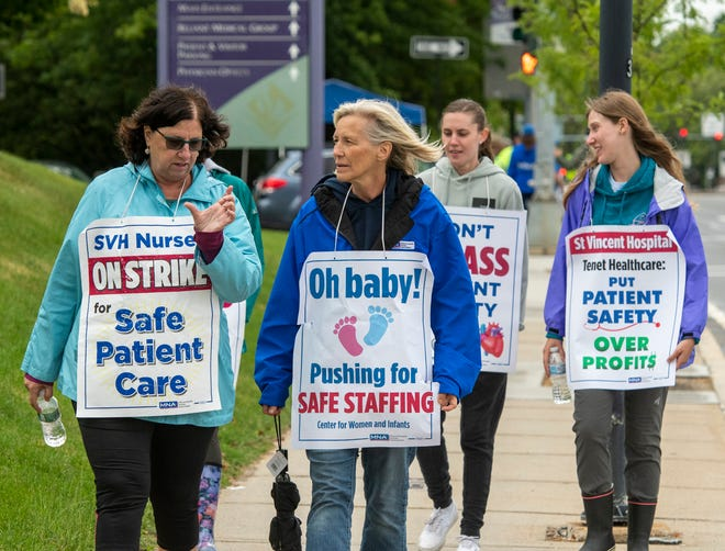 St. Vincent Hospital nurses Maureen Lavoie, left, and Claudia White along with others, walk the picket line Monday on Summer Street in Worcester.