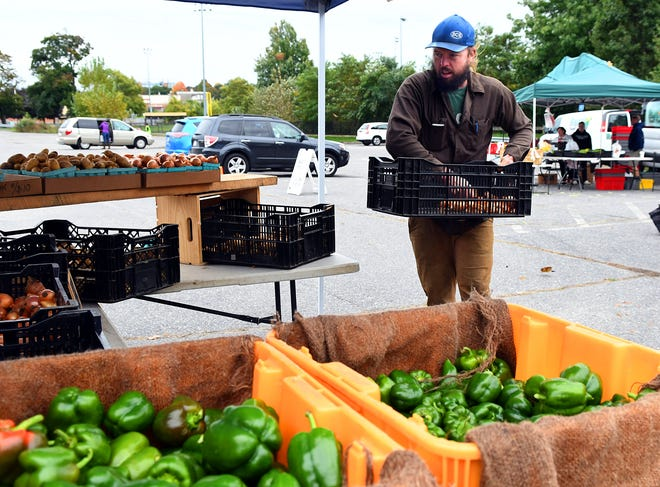 Conor Rice of Rice's Roots Farm in Petersham restocks various vegetables after the opening rush at the Regional Environmental Council farmersmarket at Beaver Brook Park in 2018.