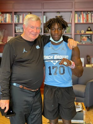 2024 Cummings running back/wide receiver Jonathan Paylor (right), pictured here with UNC football head coach Mack Brown, earned a offer from the Tar Heels after a standout camp performance this weekend.