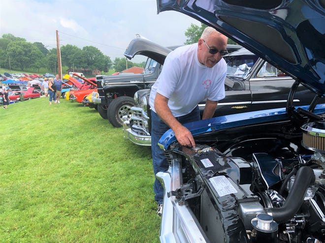 Ron Schrock checks out his engine while looking at cars at the Fabulous 50's Fling.