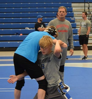 Ohio State head wrestling coach Tom Ryan guides Hunter Bittinger (Harrison Central) through a drill with TJ Wilson (Tusky Valley).