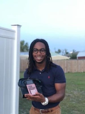 Bay County student Jonathan Walker holds his latest invention that won him a national award. The device helps address prescription drug management issues.