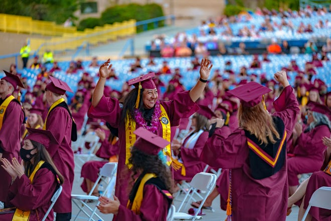 Victor Valley College graduates raise their arms in celebration at the commencement ceremony held at Glen Helen Amphitheater in Devore on June 12, 2021.