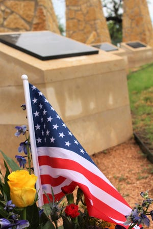 """A U.S. flag and, because this is Texas, a yellow rose and bluebonnets fill a memorial placed at Dyess Air Force Base Memorial Park for Flag Day. In the background are three """"We honor"""" stones that honor fallen airmen who served at the base. The closest remembers five airmen who died Oct. 12, 1966, near Guthrie."""
