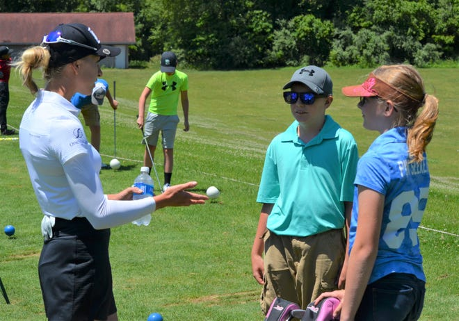 Sophia Popov talks to youth golfers Emma Bushman, right, and Brody Bushman. Popov, who won the 2020 Women's British Open, held a youth clinic at Binder Park Golf Club on Sunday.