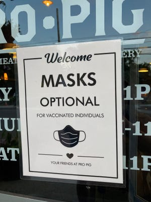 A sign outside a business lets patrons know that masks are optional for people who have been fully vaccinated against COVID-19.
